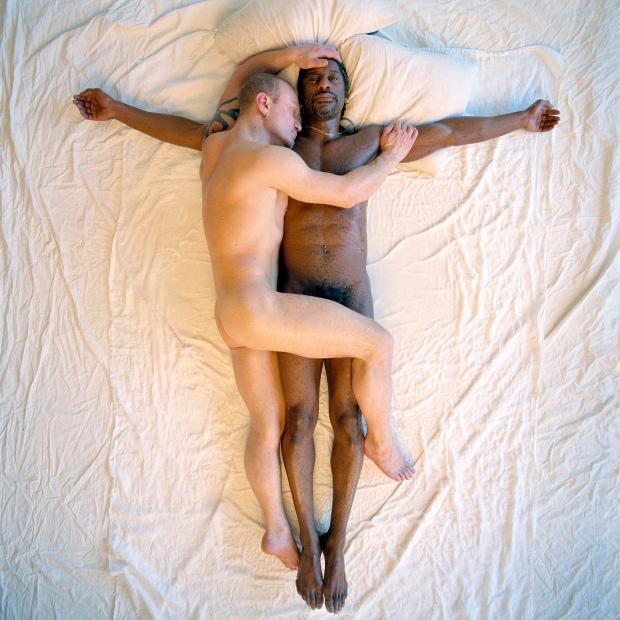 Deux hommes nus sont couché sur lit. Un homme noir repose sur le dos, les bras en croix. Un homme blanc et couché contre lui, une jambe posée sur ses jambes.