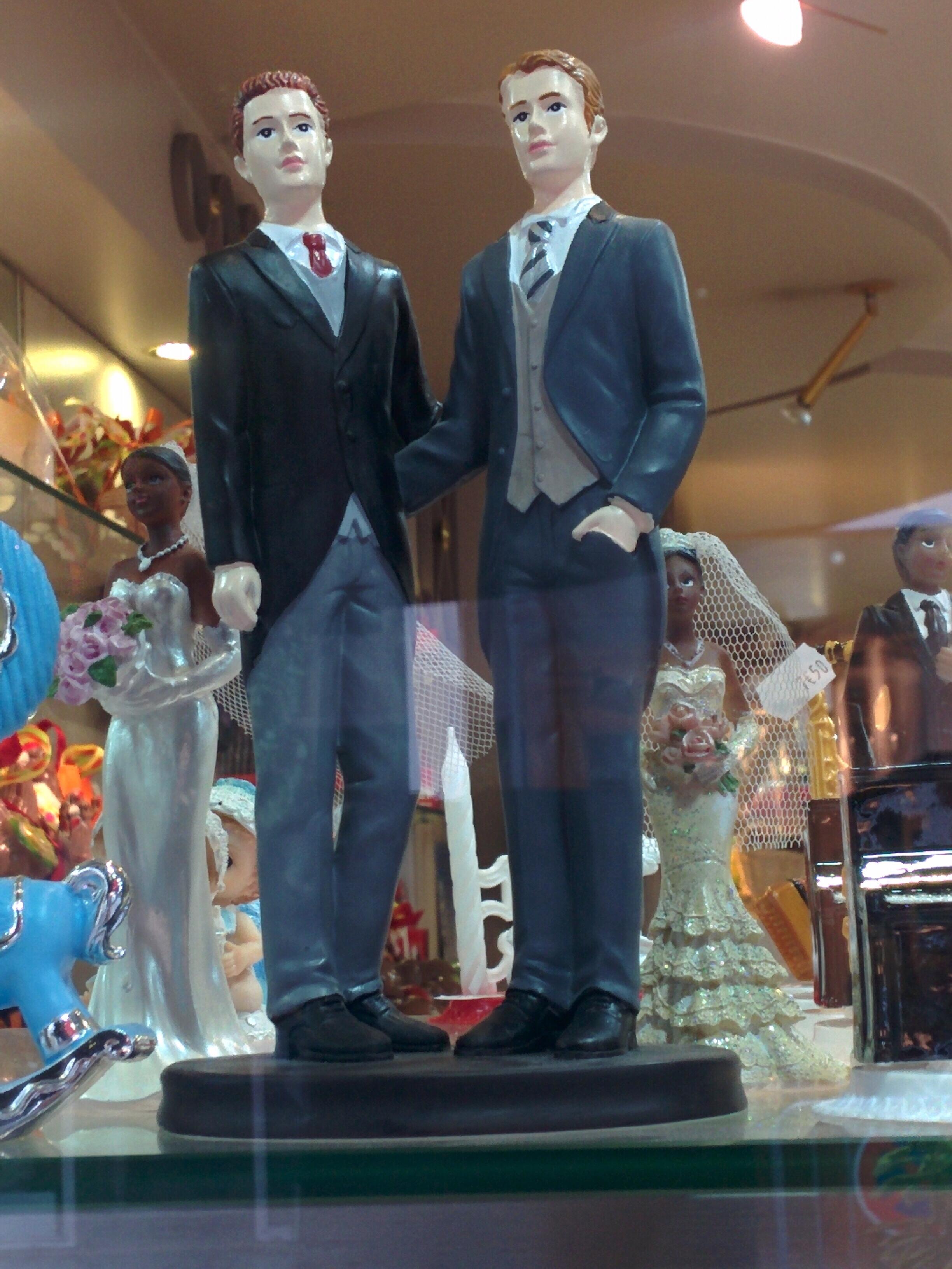 Deux hommes en tenue de marié comme figurine à placer sur un gâteau de mariage