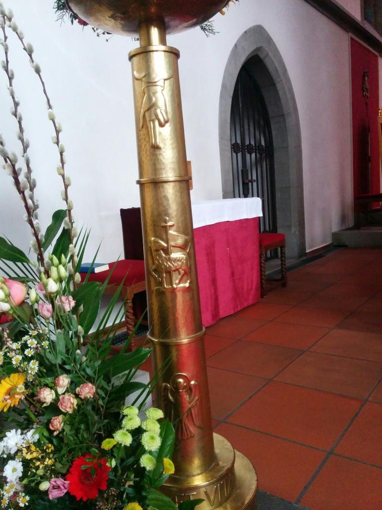 Un chandelier pascal dans la cathédrale Sankt-Florin à Vaduz, Liechtenstein. De haut en bas, la main de Dieu, l'agneau du Christ et la colombe de l'Esprit